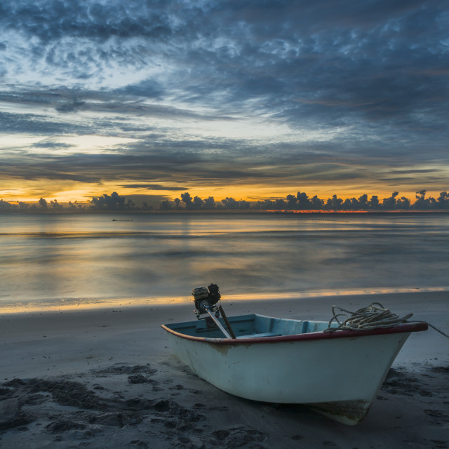 """A beautiful tropical dawn with a boat on beach"" stock image"