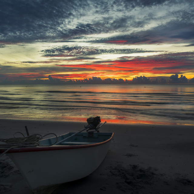 """A beautiful dawn on a topical beach with a boat"" stock image"