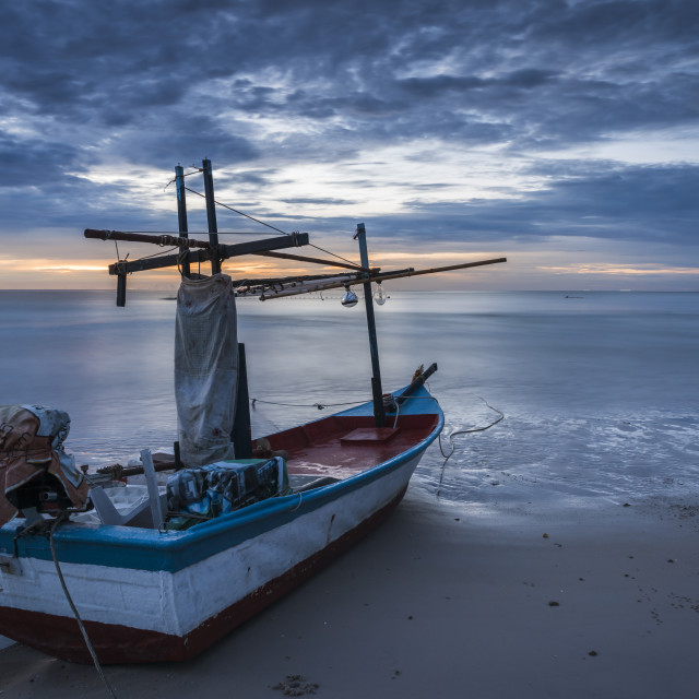 """A fishing boat on beach in dawn"" stock image"