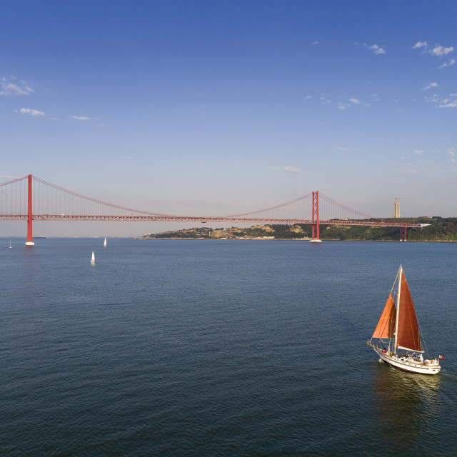 """Aerial view of a beautiful sail boat on the Tagus River with the 25 of April Bridge on the background, in the city of Lisbon, Portugal"" stock image"
