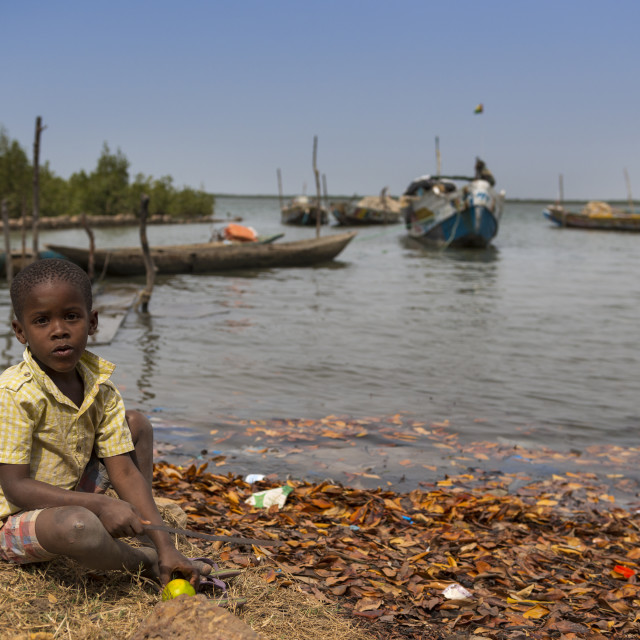 """Cacheu, Republic of Guinea-Bissau - February 1, 2018: Young boy playing next to the water in the port of the city of Cacheu, in Guinea Bissau."" stock image"