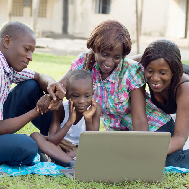 """Happy family in front of a laptop."" stock image"
