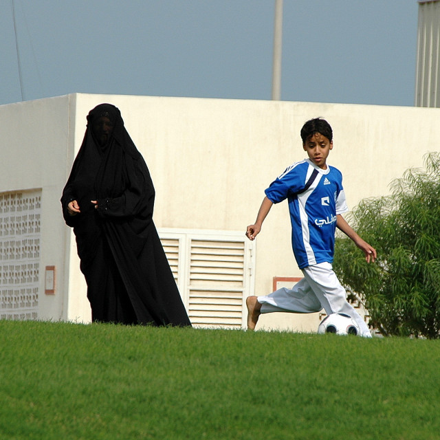 """""""Brothers and a burka-clad sister play football"""" stock image"""