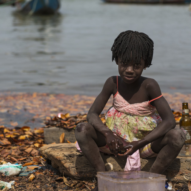 """Cacheu, Republic of Guinea-Bissau - February 1, 2018: Young girl washing bottles next to the water in the port of the city of Cacheu, in Guinea Bissau."" stock image"