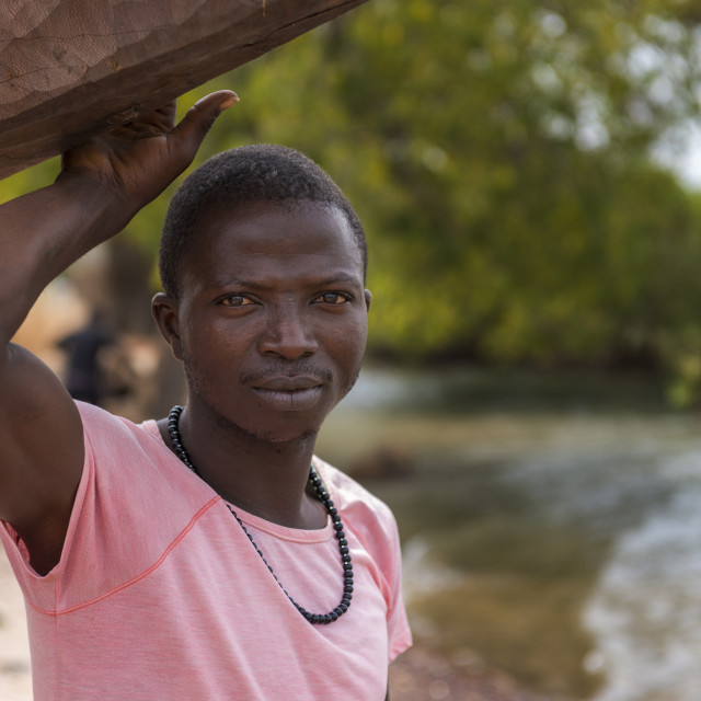 """Cacheu, Republic of Guinea-Bissau - February 1, 2018: Portrait of a young fisherman at the port of the city of Cacheu, in Guinea Bissau."" stock image"