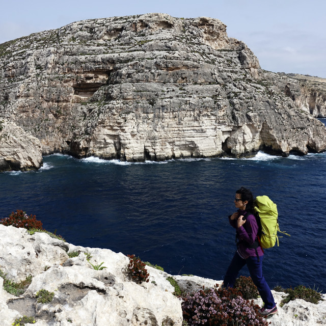 """""""A woman hiking above sea cliffs near The Blue Grotto, south Malta"""" stock image"""