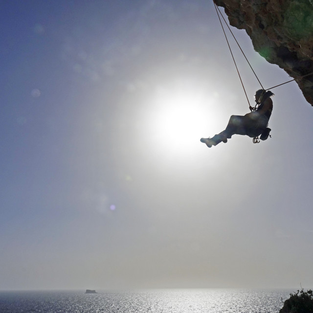 """""""Rock climber lowering off after ascending a steep climb on the cliffs of Malta"""" stock image"""