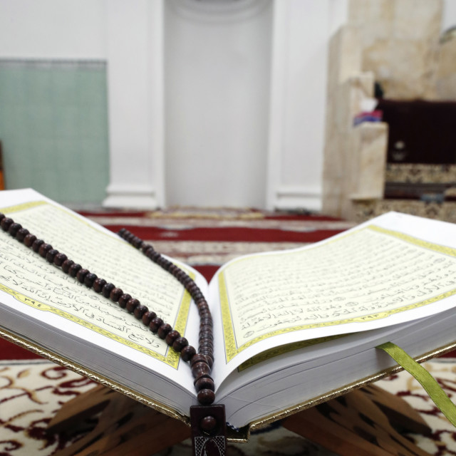 """""""An open Holy Quran and a muslim prayer beads on wood stand with mihrab in..."""" stock image"""