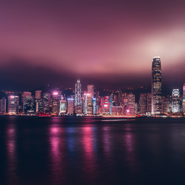 """Hong Kong skyline on Victoria Harbour with moody mist and clouds"" stock image"