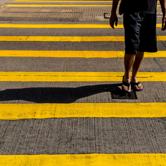 """Tourist man in shorts and sandals crossing road in Hong Kong"" stock image"