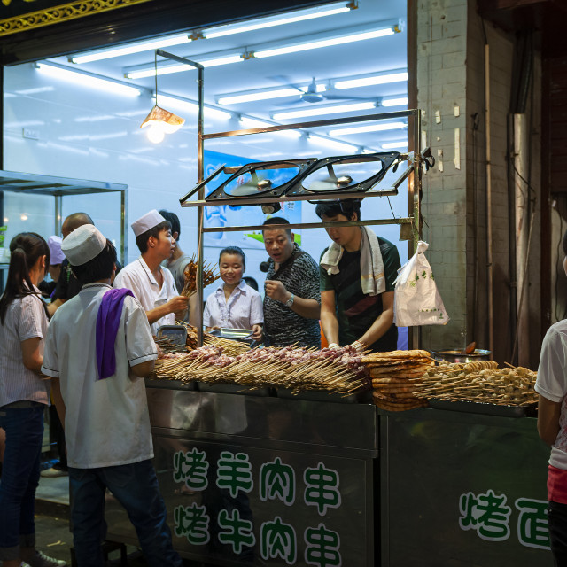 """Xian, China - August 6, 2012: People at a food stall in a street of the Muslim Quarter in the city of Xian in China, Asia"" stock image"