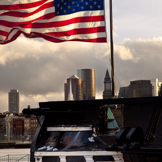 """""""American flag flying from stern of the USS Constitution with the buildings of..."""" stock image"""
