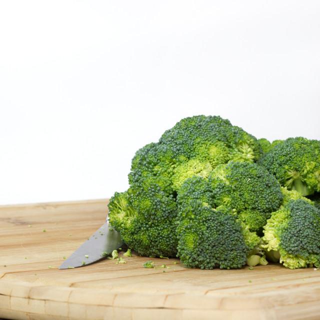"""Raw Organic Broccoli on a Wooden Cutting Board"" stock image"