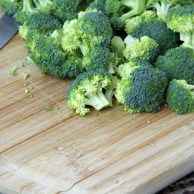 """""""Cut up Broccoli on a wooden board"""" stock image"""