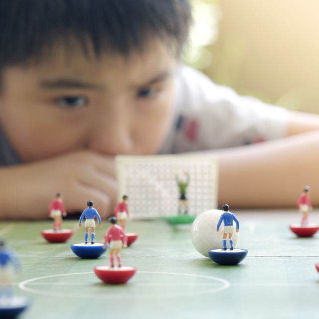 """Young Boy Playing Table Soccer Board Game"" stock image"