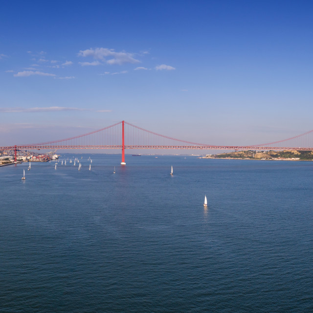 """Aerial panoramic view of the city of Lisbon with sail boats on the Tagus River and the 25 of April Bridge (Ponte 25 de Abril) on the background; Concept for travel in Portugal and visit Lisbon"" stock image"