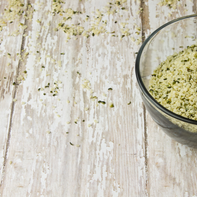 """""""Bowl of Raw Shelled Hemp Seeds on a Wood Plank Board"""" stock image"""