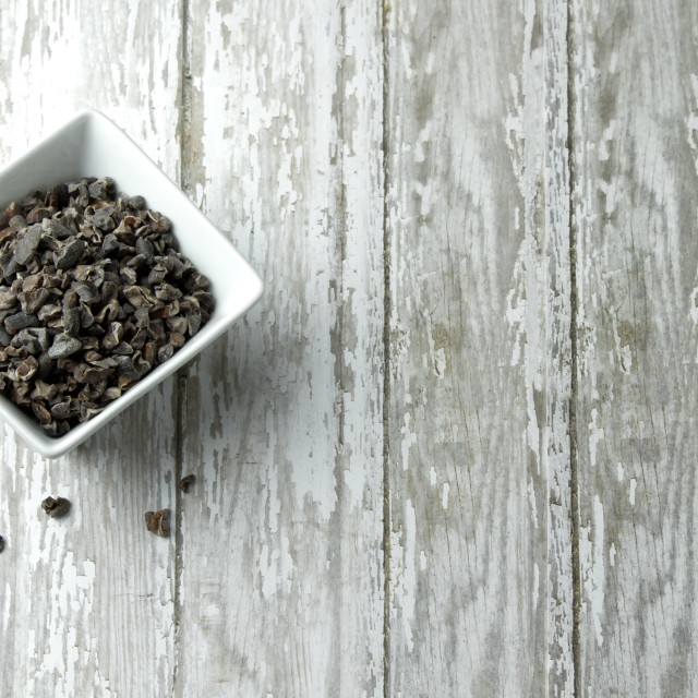 """""""Bowl of Organic Cacao Nibs on a wood plank board"""" stock image"""