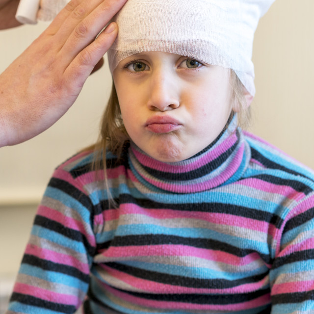 """""""Doctor makes a bandage of young girl's head after plastic surgery. verical photo"""" stock image"""