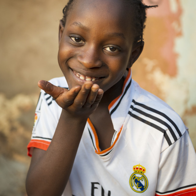 """Bissau, Republic of Guinea-Bissau - January 31, 2018: Portrait of a smiling young girl at the Cupelon de Cima neighborhood in the city of Bissau, Guinea Bissau"" stock image"