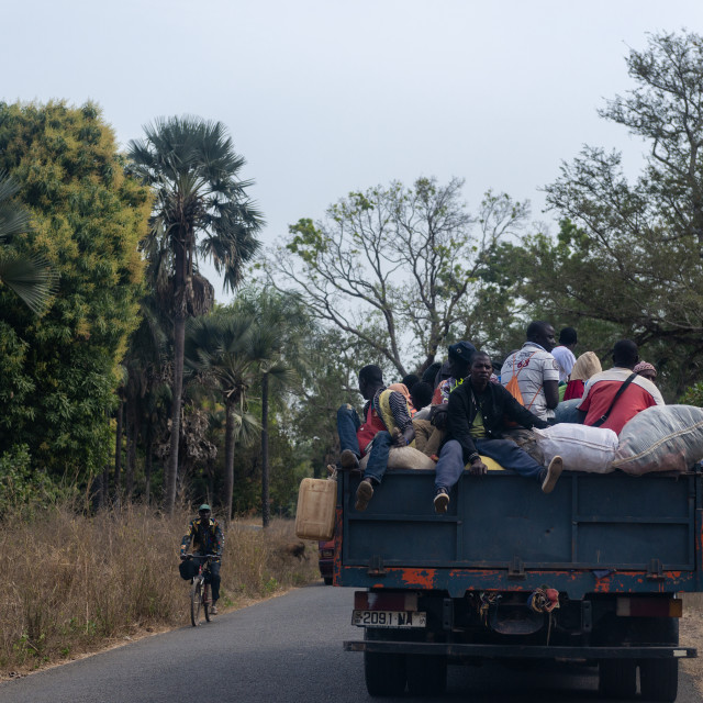 """Cacheu, Republic of Guinea-Bissau - February 1, 2018: People traveling in the back of a truck in Cacheu Region, in Guinea Bissau."" stock image"