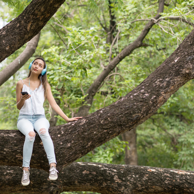 """""""happy woman listen to streaming music on big tree"""" stock image"""