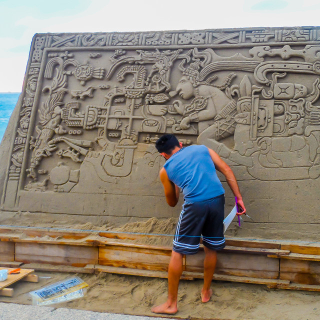"""Artist at work on sand mural"" stock image"