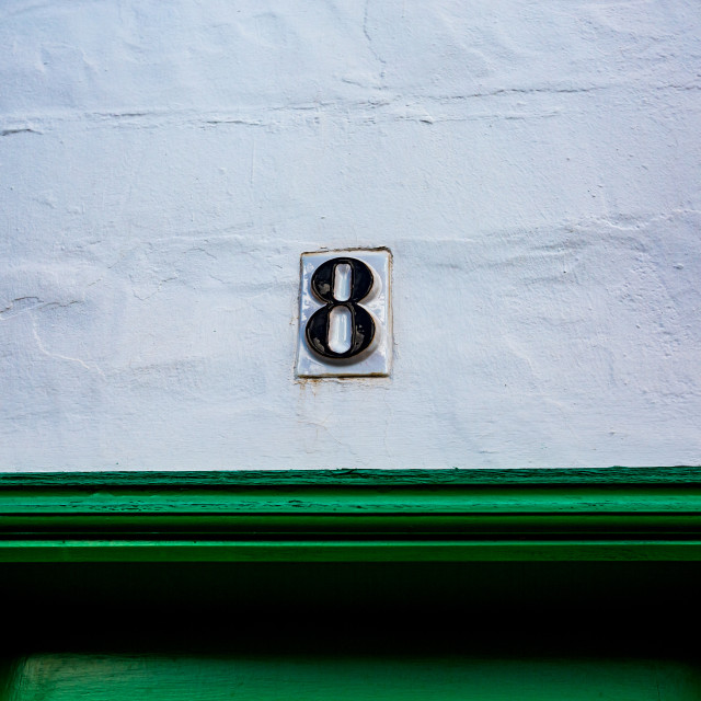 """""""Ceramic black number 8 white wall over green door"""" stock image"""
