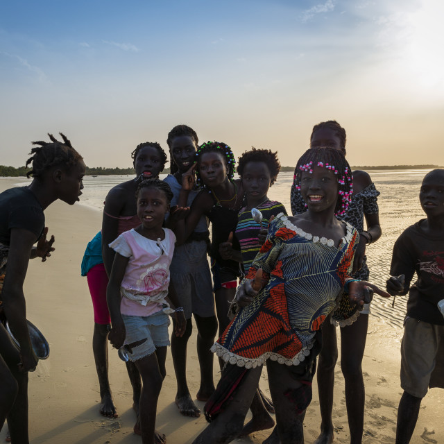 """Group of children playing by the beach in the island of Orango at sunset, in Guinea Bissau; Orango is part of the Bijagos Archipelago."" stock image"