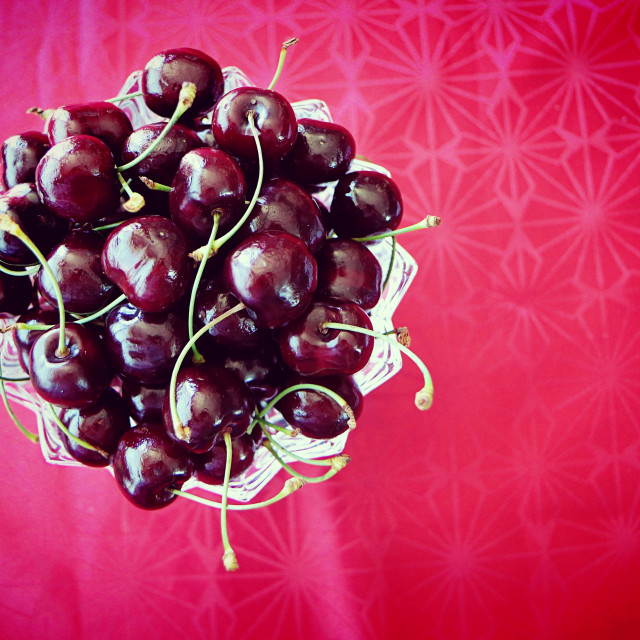 """Dark red ripe cherries on red background"" stock image"