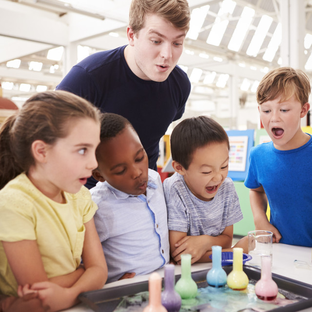 """""""School kids and teacher watch experiment at a science centre"""" stock image"""