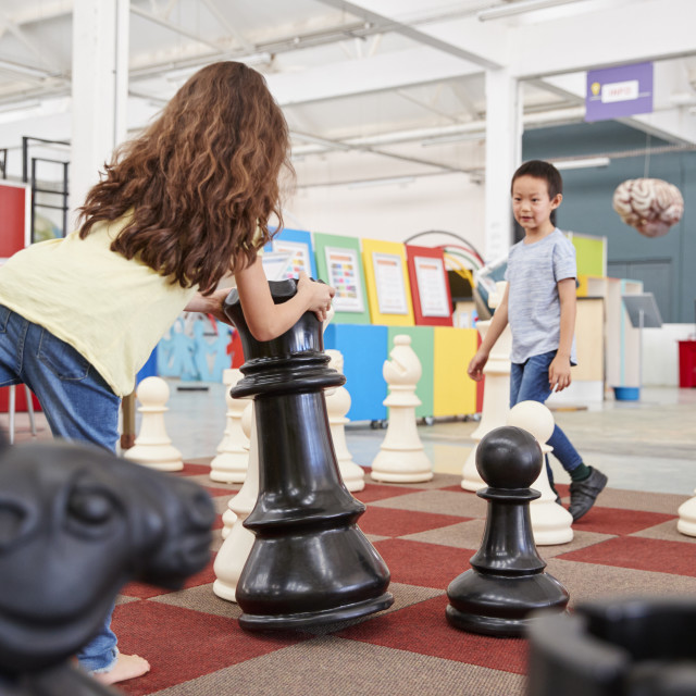 """""""Two children playing giant chess at a science centre"""" stock image"""