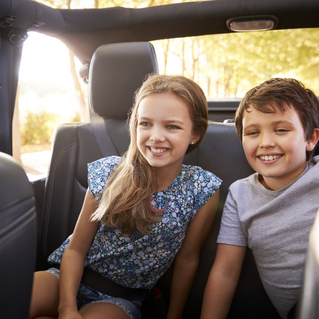 """""""Children Sitting In Back Seat Of Open Top Car On Road Trip"""" stock image"""
