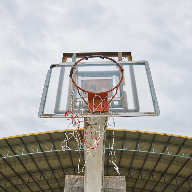 """Old abandoned basketball shield with broken ring and net"" stock image"