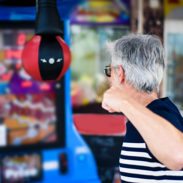 """Senior man punching the boxer arcade"" stock image"
