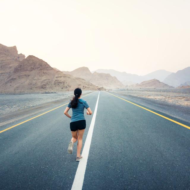 """""""Female running on the desert road"""" stock image"""