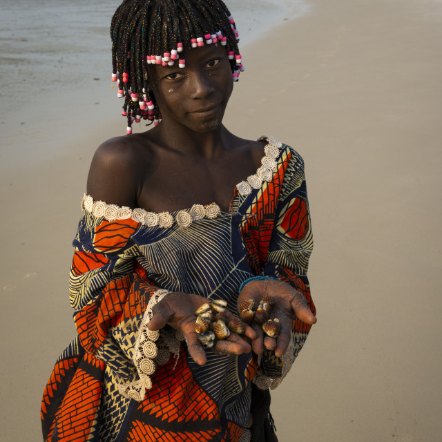 """Orango Island, Guinea-Bissau - February 2, 2018: Portrait of a young cockles harvester in the beach in the island of Orango at sunset."" stock image"