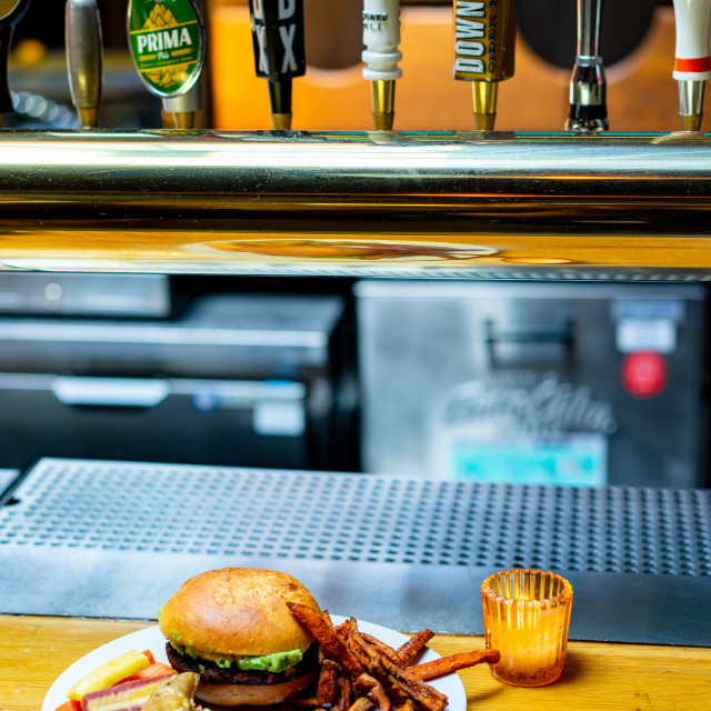 """Burger and sweet potato fries at a bar under beer taps"" stock image"