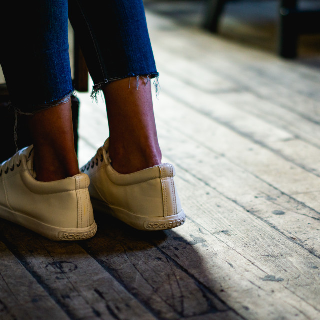 """Girl standing on a wooden floor with white shoes"" stock image"