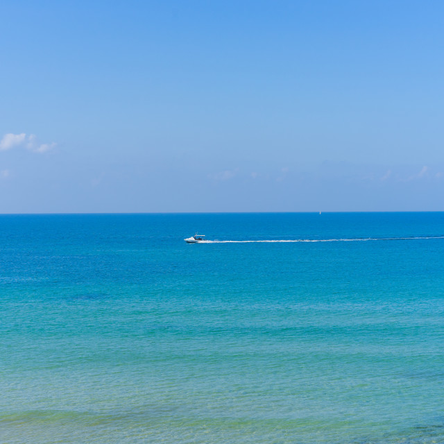 """Calm water with a boat in the distance at the beach in Tel Aviv, Israel"" stock image"
