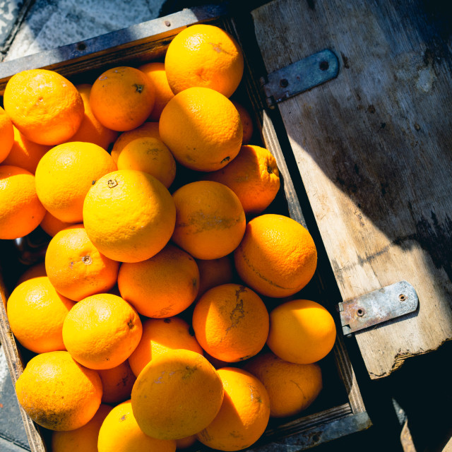 """Oranges in a rustic wood basket in bright sunlight"" stock image"