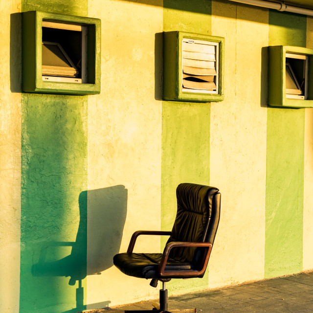 """Desk chair sitting outside in the sun against a green stripped wall"" stock image"