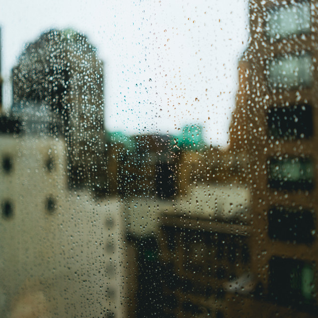 """Rain drop covered window with city buildings in the background"" stock image"