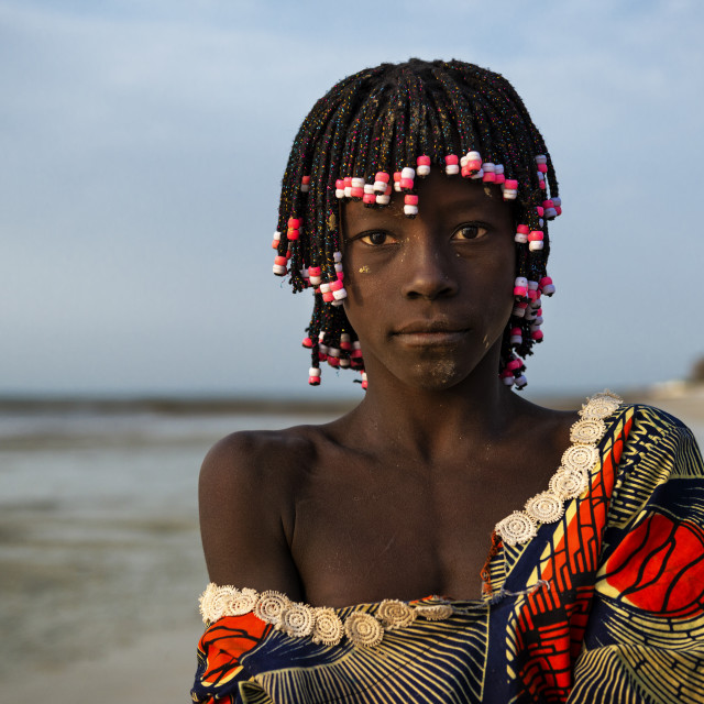 """Orango Island, Guinea-Bissau - February 2, 2018: Portrait of a beautiful young girl in the beach in the island of Orango at sunset."" stock image"