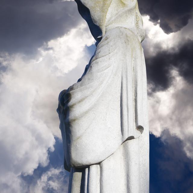 """faceless monk statues against dark skies"" stock image"