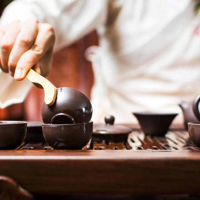 """Tea ceremony, woman cleaning teacup with boiled water"" stock image"