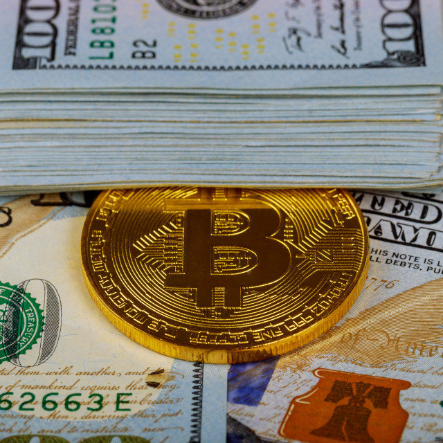 """Gold bitcoin coins on one hundred US dollar bills background. Cryptocurrency,..."" stock image"