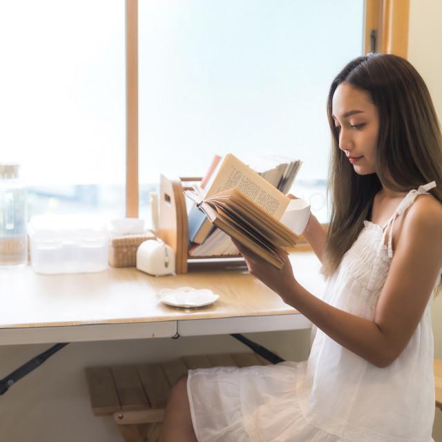 """girl read book and drink coffee near window"" stock image"