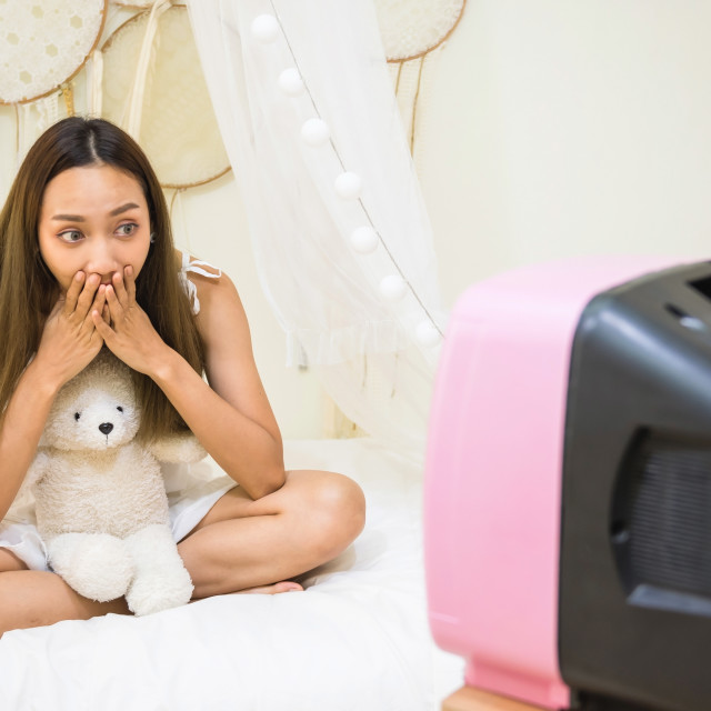 """""""Excited Asian woman watch horror movie on bed"""" stock image"""