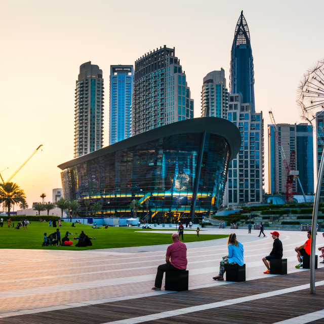"""Dubai, United Arab Emirates - May 18, 2018: People enjoying sunset with Dubai opera building and modern skyscrapers of the Dubai mall surroundings view"" stock image"
